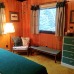 another chair for reading, dresser, pillows and cozy blankets for a chilly night